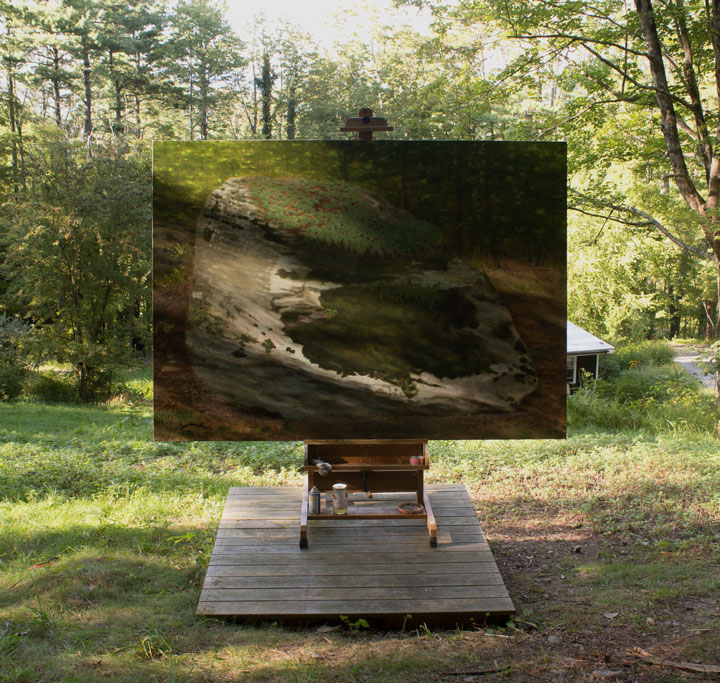 a large painting of a rock on an easel